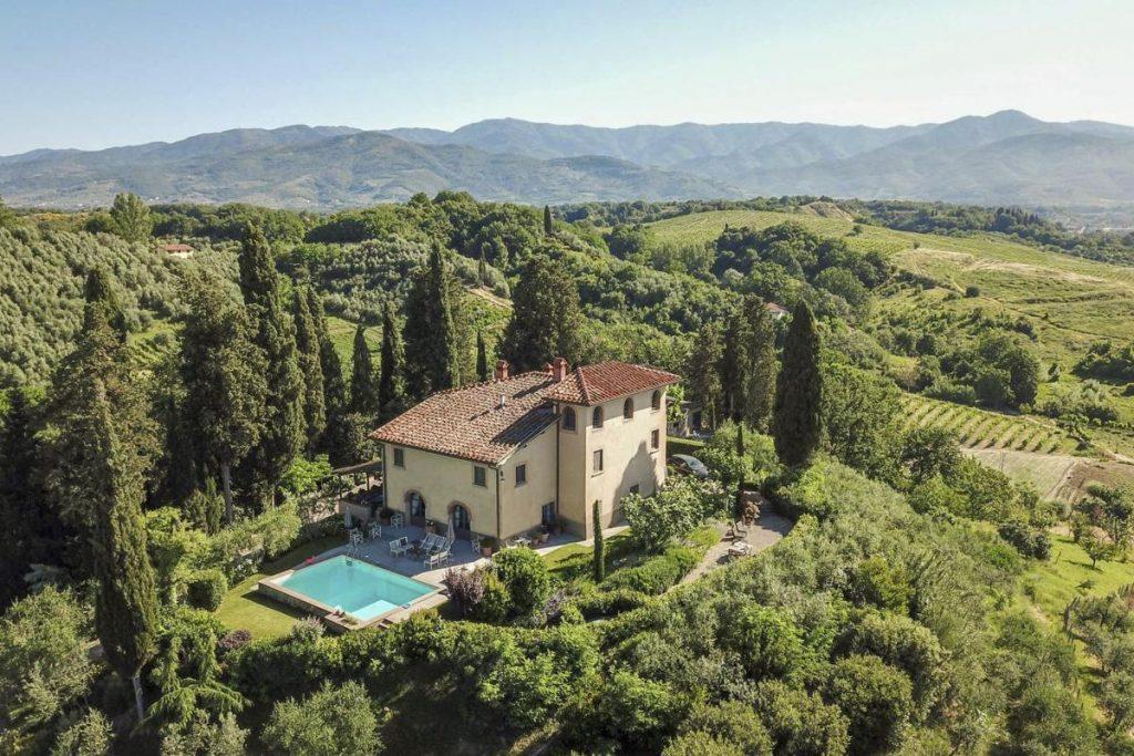 Drone views Private villa rental in Italy, Arezzo with a pool.